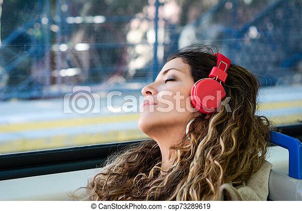 Una mujer urbana durmiendo en un tren viaja al lado de la ventana. - csp73289619