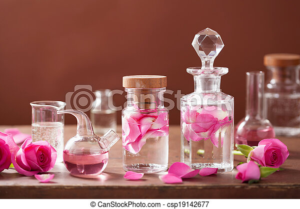 alchemy and aromatherapy set with rose flowers and flasks - csp19142677