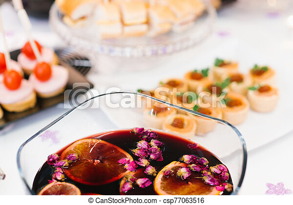 alcoholic cold mulled wine with orange juice in a bowl with rose buds - csp77063516