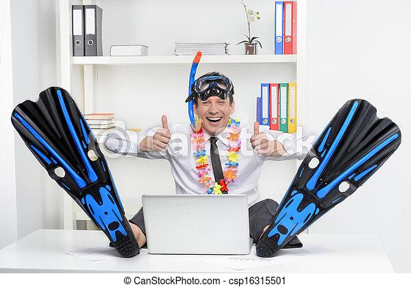 Listo para las vacaciones. Hombre de negocios alegre en aletas y snorkel sentado en su lugar de trabajo y sonriendo a la cámara - csp16315501
