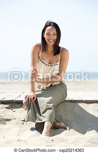Una joven alegre sentada en la playa - csp20214363