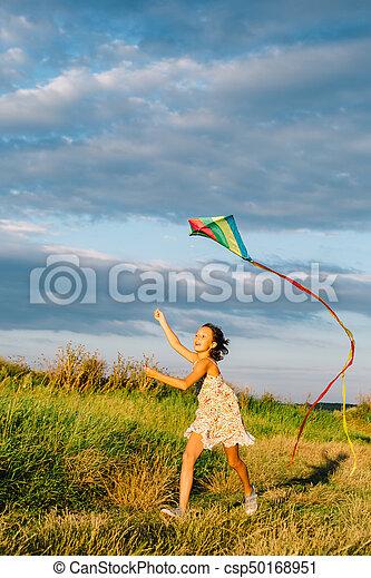 Chica alegre corriendo con cometa - csp50168951