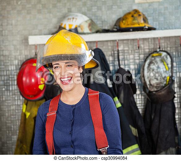 Una alegre bombero en la estación de bomberos - csp30994084