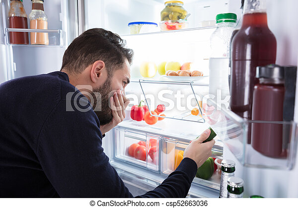El hombre nota el olor que viene de la comida sucia en el refrigerador - csp52663036