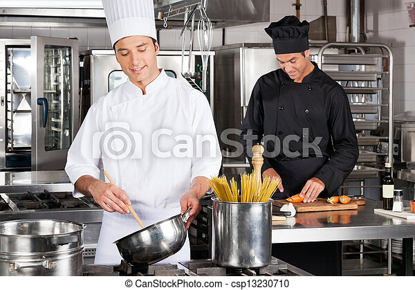 Felices chefs preparando comida - csp13230710