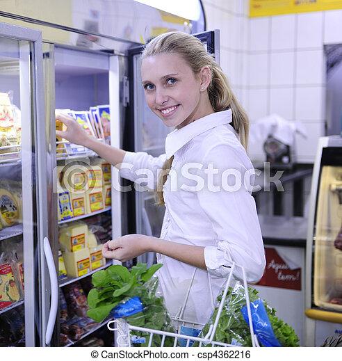 Una mujer comprando comida congelada en el supermercado - csp4362216