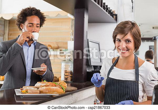 Feliz servidor preparando comida en el mostrador - csp21867033