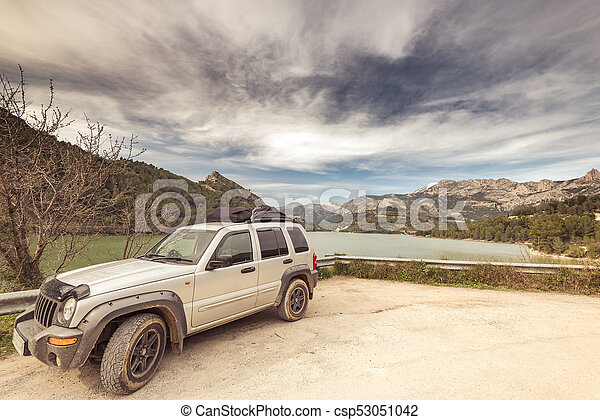 All terain car by lake in mountains, road trip concept. - csp53051042