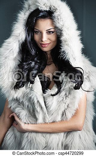 Alluring brunette woman wearing stylish fur coat - csp44720299