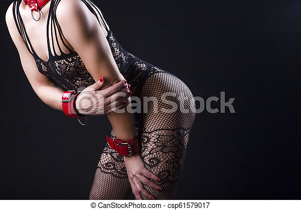 Alluring Caucasian Female in Sexy Mesh Body Suit Prepared for Sado-Masochism Play. Bent Backwards Over Black Background. Bent Forward. - csp61579017