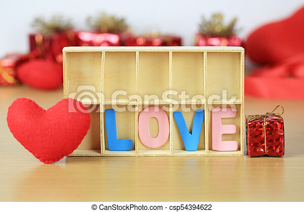 alphabet of LOVE in wooden box near red heart shape and gift box on wooden floor. - csp54394622