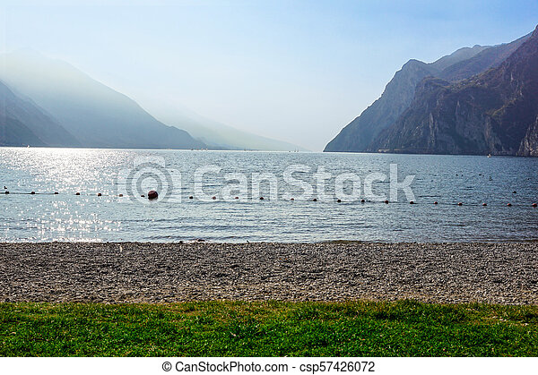 alpine landscape at sunset with lake beach and mountains on the horizon . - csp57426072