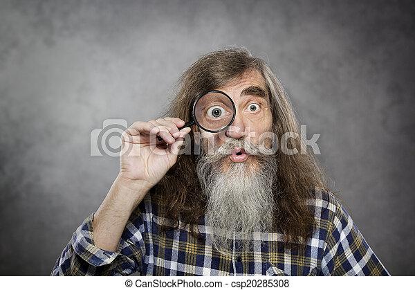 Senior alter Mann, der durch die Vergrößerungsglas schaut - csp20285308