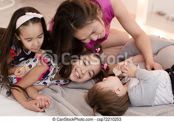 Una familia joven con niños pequeños. El concepto de una gran familia feliz. Abrazos de seres queridos - csp72210253