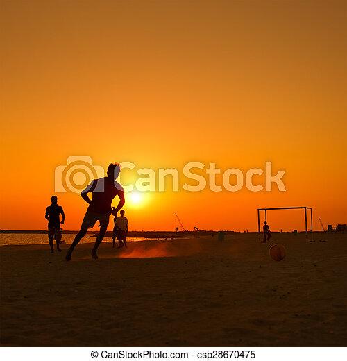 amateur football at beach during sunset - csp28670475