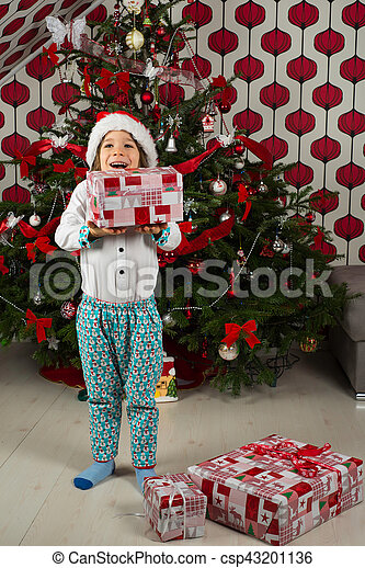 Amazed kid holding Christmas gifts - csp43201136  sc 1 st  Can Stock Photo & Amazed kid holding christmas gifts. Amazed cheerful kid dressed in ...