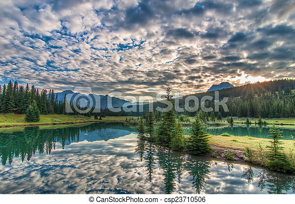 Amazing Clouds and Trees Reflected in Lake - csp23710506