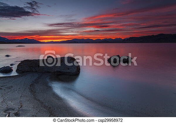 Amazing red sunset over a mountain lake. - csp29958972