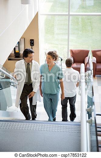 Doctor y enfermera discutiendo mientras caminan por las escaleras - csp17853122