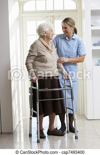 Carer ayudando a la anciana usando un marco andante - csp7493400
