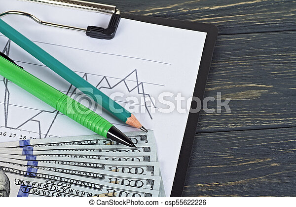 American dollars, pencils and a chart on a wooden background - csp55622226