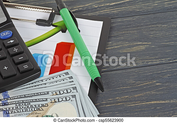 American dollars, pencils and a chart on a wooden background. Business concept. - csp55623900