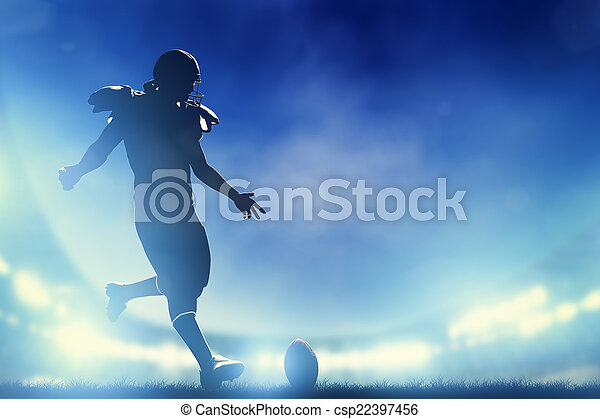 American football player kicking the ball, kickoff. Stadium lights - csp22397456