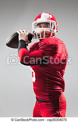 American football player posing with ball on white background - csp35304070