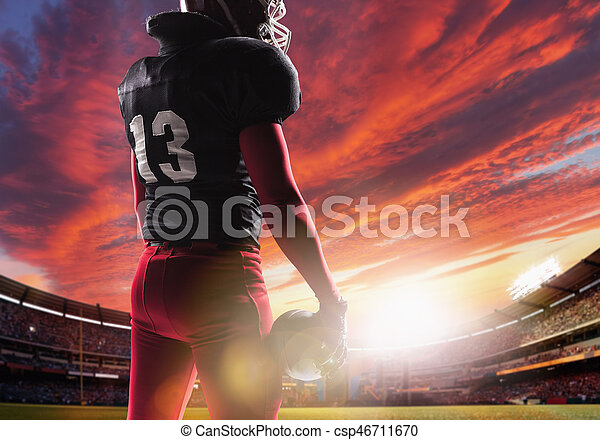 American football player posing with ball on stadium background - csp46711670