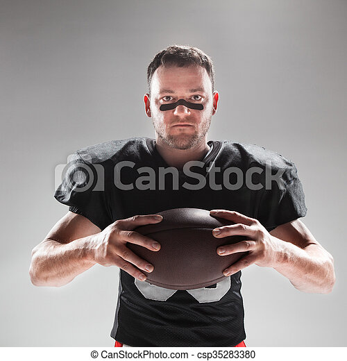American football player posing with ball on white background - csp35283380