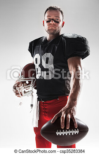 American football player posing with ball on white background - csp35283384