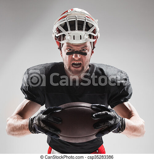 American football player posing with ball on white background - csp35283386