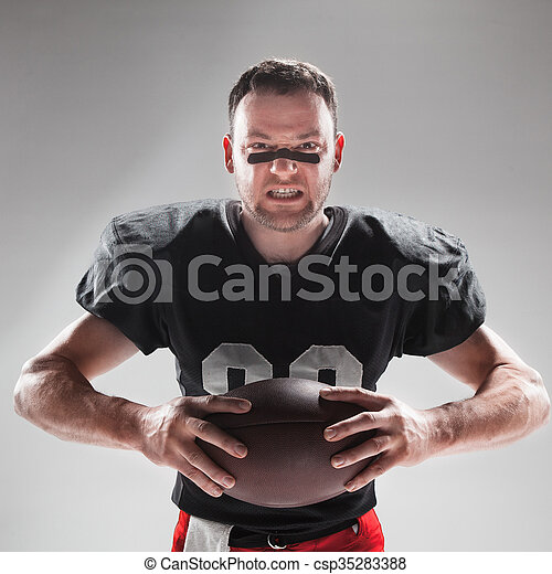 American football player posing with ball on white background - csp35283388