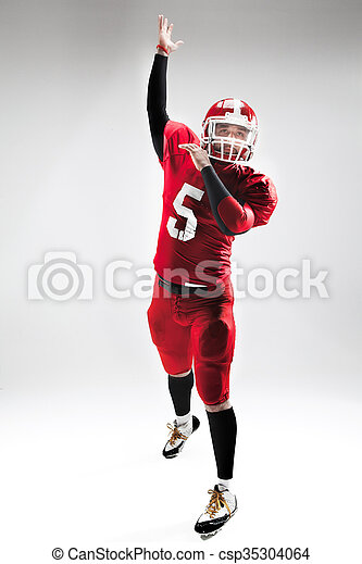 American football player posing with ball on white background - csp35304064