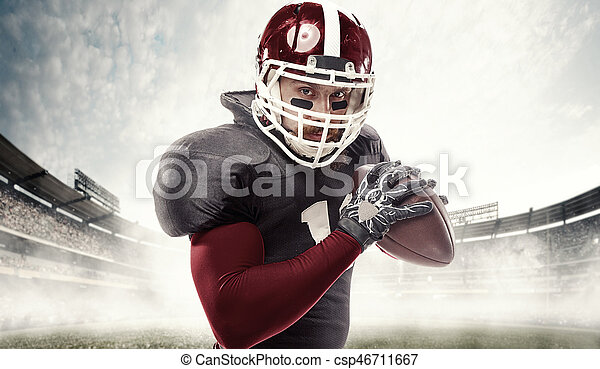 American football player posing with ball on stadium background - csp46711667