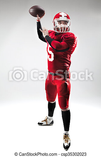 American football player posing with ball on white background - csp35302023