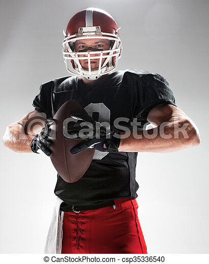 American football player posing with ball on white background - csp35336540