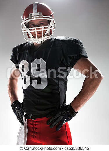 American football player posing with ball on white background - csp35336545