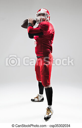 American football player posing with ball on white background - csp35302034