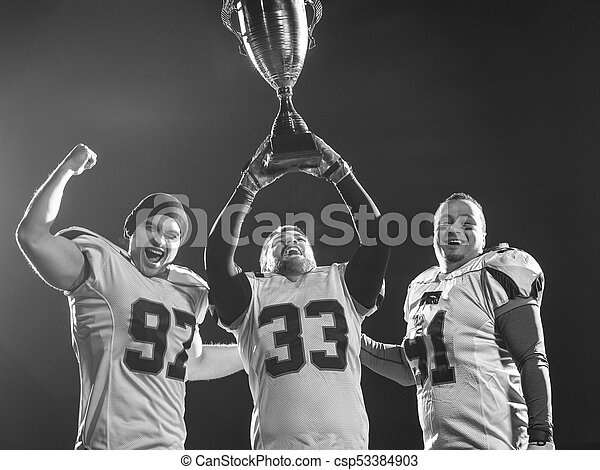 american football team with trophy celebrating victory - csp53384903