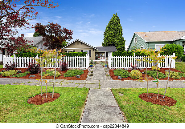 American House Exterior With Beautiful Front Yard Landscape Design And White Wooden Fence Canstock