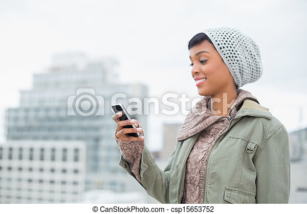 Amused young model in winter clothes looking at her mobile phone outside on a cloudy day - csp15653752