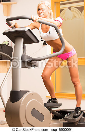 An attractive young woman using a step machine in the gym - csp15900091