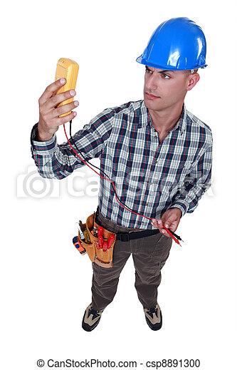 An electrician checking his voltmeter. - csp8891300