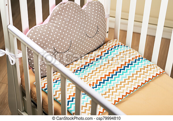 An empty baby white crib with a cute brown pink pillow with a can. brown mattress. Cozy bed for the baby - csp79994810