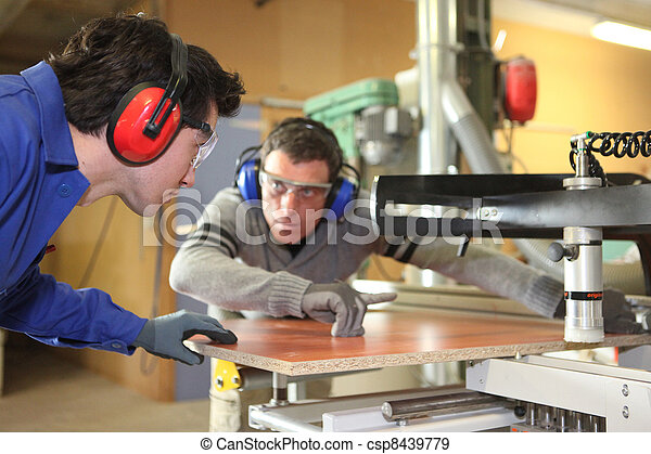 An experienced worker showing an apprentice how to cut a piece of wood using a machine - csp8439779