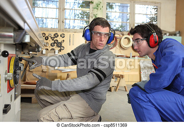 An experienced workman showing an apprentice the ropes - csp8511369