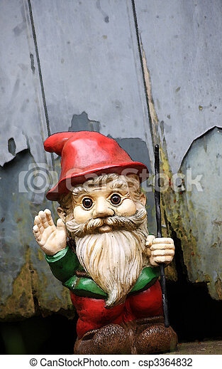 An illustration of a small bearded garden gnome with a red peeked hat waving its hand and holding a staff. Set at a slight angle against a shed door with peeling paint. Copy space avilable. - csp3364832