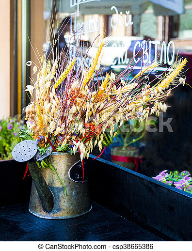 an iron watering can with flowers - csp38665386
