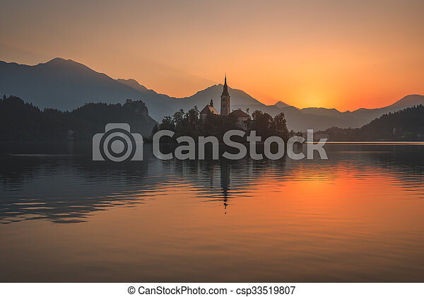 Little Island with Catholic Church in Bled Lake, Slovenia at Beautiful Colorful Sunrise with Castle and Mountains in Background